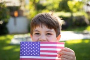 Portrait close up of a young Caucasian boy with short brown hair and blue eyes outside in a sunny garden holding a US flag and smiling to camera. Family enjoying time at home, lifestyle concept